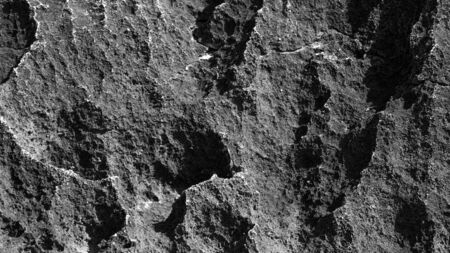 large texture of a large black stone. contrasting light on the stone Фото со стока