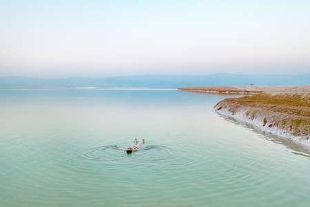 woman bathes in twoman bathes in the dead sea. Aerial view he dead sea. Aerial view. High quality photo Фото со стока