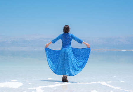 girl in a blue dress on the shores of the dead sea in Israel on a sunny day. beautiful nature of the dead sea and a woman looks at this nature with admiration. Beach at Ein Bokek Archivio Fotografico - 151731894