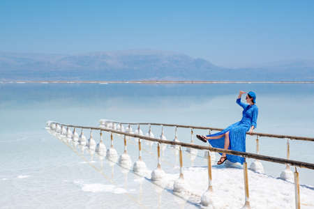 girl in a blue dress on the shores of the dead sea in Israel on a sunny day. beautiful nature of the dead sea and a woman looks at this nature with admiration. Beach at Ein Bokek Archivio Fotografico