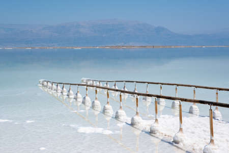 shores of the dead sea in Israel on a sunny day. beautiful nature of the dead sea and . Beach at Ein Bokek. railing to the sea Archivio Fotografico - 151731935