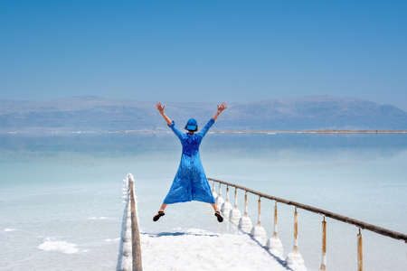 girl in a blue dress on the shores of the dead sea in Israel on a sunny day. beautiful nature of the dead sea and a woman looks at this nature with admiration. Beach at Ein Bokek Archivio Fotografico - 151732608