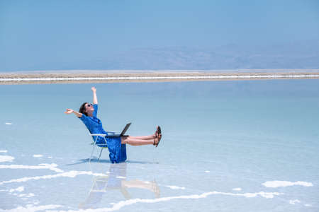 woman freelancer works at a laptop on the shores of the dead sea in israel. recreation and remote work concept. beautiful landscape ein bokek in israel Archivio Fotografico - 151732816