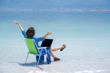 woman freelancer works at a laptop on the shores of the dead sea in israel. recreation and remote work concept. beautiful landscape ein bokek in israel