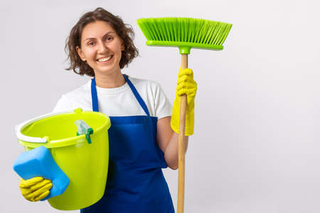 woman cleans the house. The woman is holding a mop and a bucket and gloves and a cleaning sponge. indoor cleaning concept Archivio Fotografico