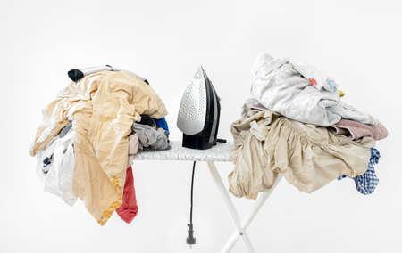 iron on ironing board against white wall background. High quality photoiron on ironing board against white wall background. dirty laundry before ironing after washing Фото со стока