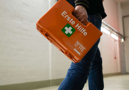 first responder: First aid after an accident at work. First responder with first aid kit, Germany.