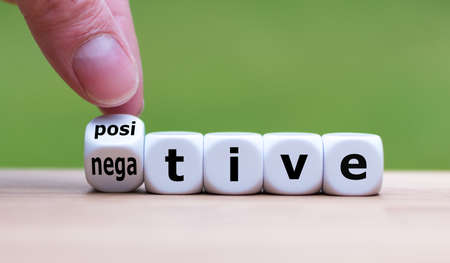 """Hand turns a dice and changes the expression """"negative"""" to """"positive"""". Stock fotó"""