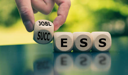 """Concept of a turning point in life. Hand turns a cube and changes the word """"jobless"""" to """"success""""."""