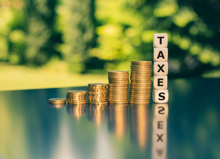 Symbol for increasing taxes. Dice form the word taxes next to increasing high stacks of coins.