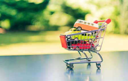 A miniature shopping cart full of cars.