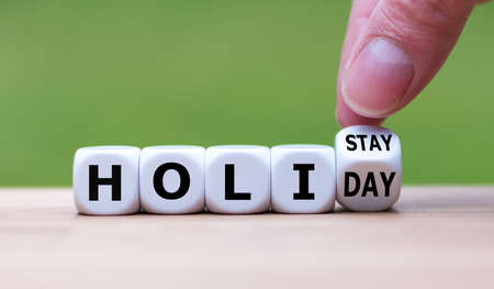 Holiday at home concept. Hand turns a cube and changes the word holiday to holistay.
