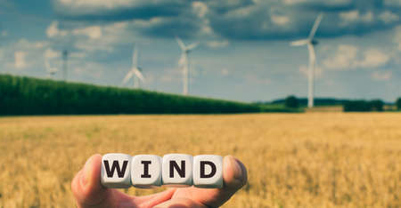 Dice form the word wind in front of a wind park.