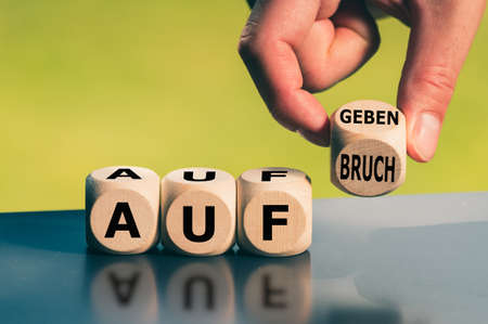 Hand turns a cube and changes the German word Stockfoto