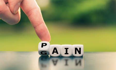 No pain no gain. Hand turns a dice and changes the word Stockfoto