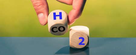 Wechsel zu Brennstoffzellenfahrzeugen. Hand wirft einen Würfel und ändert den Ausdruck CO2 in H2. Standard-Bild