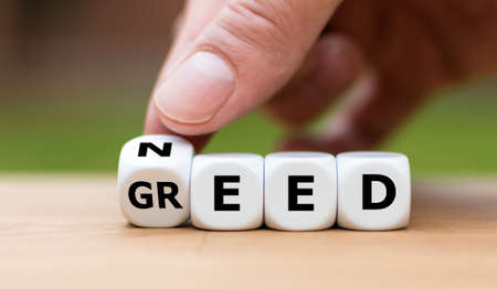 Need or Greed? Hand turns a dice and changes the word