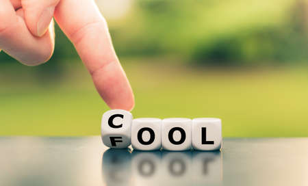 """Be cool or a fool? Hand turns a dice and changes the word """"fool"""" to """"cool""""."""