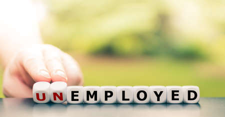 """Hand turns a dice and changes the word """"unemployed"""" to """"employed""""."""
