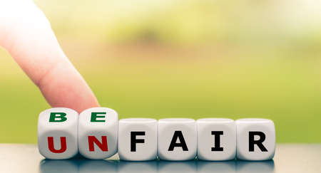 """Hand turns a dice and changes the expression """"unfair"""" to """"be fair""""."""