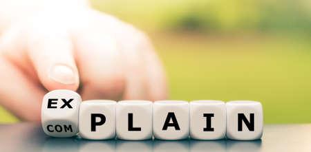 Expliquer au lieu de se plaindre. La main tourne les dés et change le mot « se plaindre » en « expliquer ». Banque d'images
