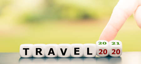 """No travelling in 2020 due to the coronavirus. Hand turns dice and changes the expression """"travel 2020"""" to """"travel 2021""""."""