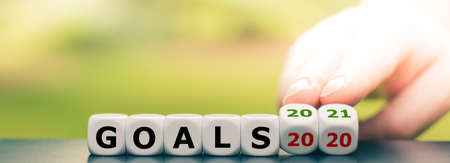 """Hand turns dice and changes the expression """"goals 2020"""" to """"goals 2021"""""""