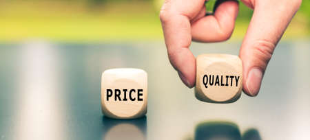 """Price versus Quality. The cube with the word """"quality"""" is selected by a hand."""