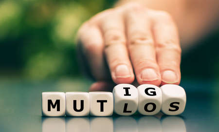 """Hand turns dice and changes the German word """"mutlos"""" (""""discouraged"""") to """"mutig"""" (""""courage""""). Banque d'images"""