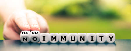 "Hand turns dice and changes the expression ""no immunity"" to ""herd immunity""."