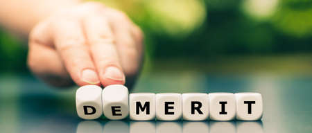 Hand turns dice and changes the word demerit to merit.