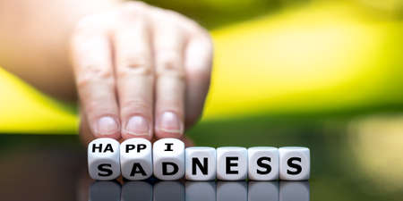 Hand turns dice and changes the word sadness to happiness.