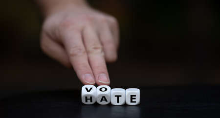 Vote instead of hate. Hand turns dice and changes the word