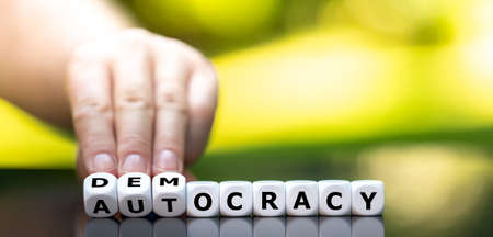"""Hand turns dice and changes the word """"autocracy"""" to """"democracy""""."""