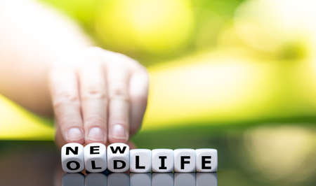 """Hand turns a dice and changes the expression """"old life"""" to """"new life""""."""