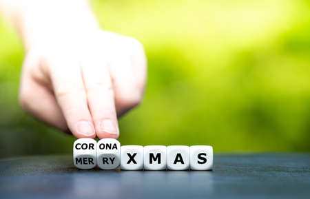 """Symbol for a corona influenced Christmas. Hand turns dice and changes the expression """"merry xmas"""" to """"corona xmas""""."""