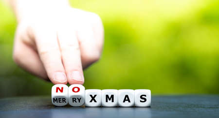 """Symbol for a corona influenced Christmas. Hand turns dice and changes the expression """"merry xmas"""" to """"no xmas""""."""