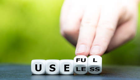 """Hand turns dice and changes the word """"useless"""" to """"useful""""."""