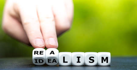 "Hand turns dice and changes the word ""idealism"" to ""realism""."