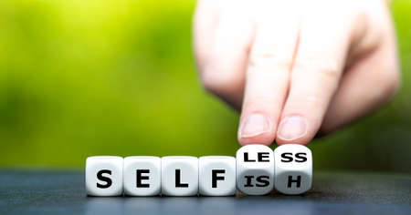 """Hand turns dice and changes the word """"selfish"""" to """"selfless""""."""