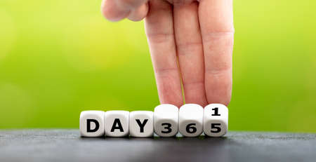 """Symbol for a new year. Hand turns dice and changes the expression """"day 365"""" to """"day 1""""."""