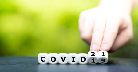 """Symbol that the world has to deal with covid 19 in the year 2021. Hand turns dice and changes the expression """"covid 19"""" to """"covid 21""""."""