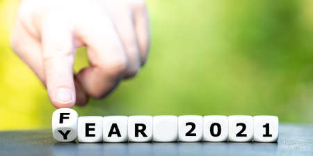 """Hand turns dice and changes the expression """"year 2021"""" to """"fear 2021""""."""
