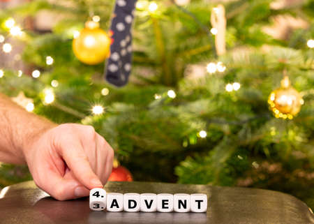 """Hand turns dice and changes the German expression """"3. Advent"""" (3rd advent) to """"4. Advent"""" (4th advent)."""