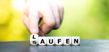 """New year resolution. Hand turns dice and changes the German word """"saufen"""" (booze) to """"laufen """"(running)."""