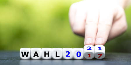 """Hand turns dice and changes the German expression """"Wahl 2017"""" (election 2017) to """"Wahl 2021"""" (election 2021)."""