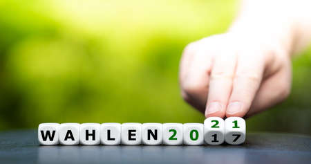 """Hand turns dice and changes the German expression """"Wahlen 2017"""" (elections 2017) to """"Wahlen 2021"""" (elections 2021)."""