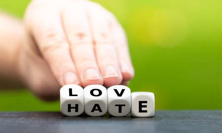 Hand turns dice and changes the word hate to love.