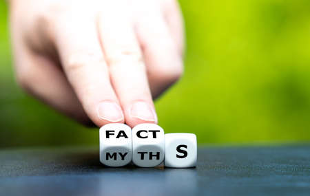 Hand turns dice and changes the word myths to facts.