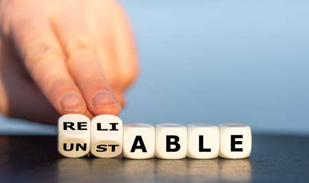 Hand turns dice and changes the word unstable to reliable.